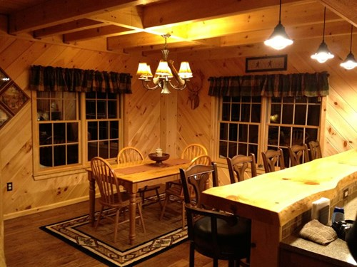 Diagonal wood paneling in log home dining room.