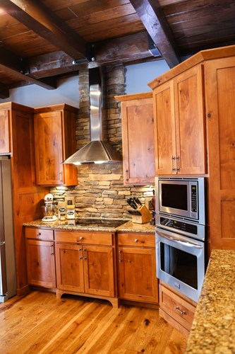 Log home kitchen with double wall ovens and a wall-chimney hood.