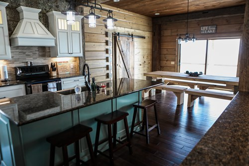 Lake house kitchen with turquoise center island and picnic dining table.