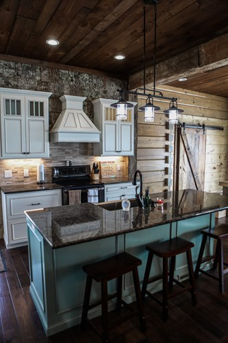 Turquoise kitchen island in lake house with three bar stools.