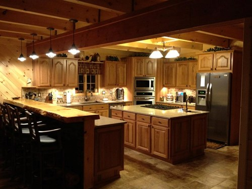 Log cabin kitchen with wood cabinets, island, and a raised bar top.