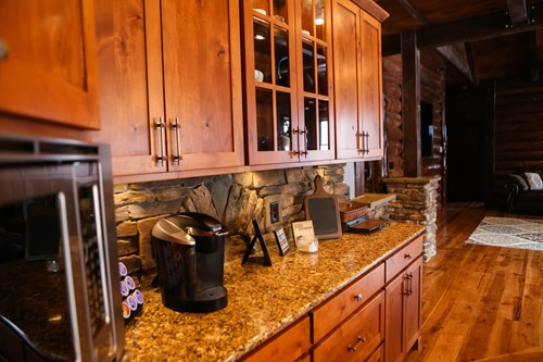 Log home kitchen with granite countertops and stone backsplash.