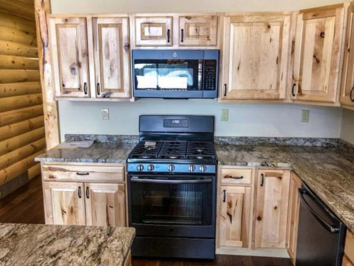 Knotty pine kitchen cabinets with marble countertops.