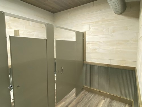 Public bathroom with whitewash shiplap and ranch rusted steel wainscotting.