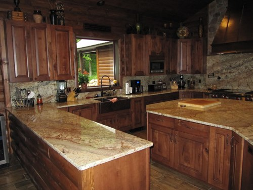 Dark wood kitchen cabinets and light marble countertops.