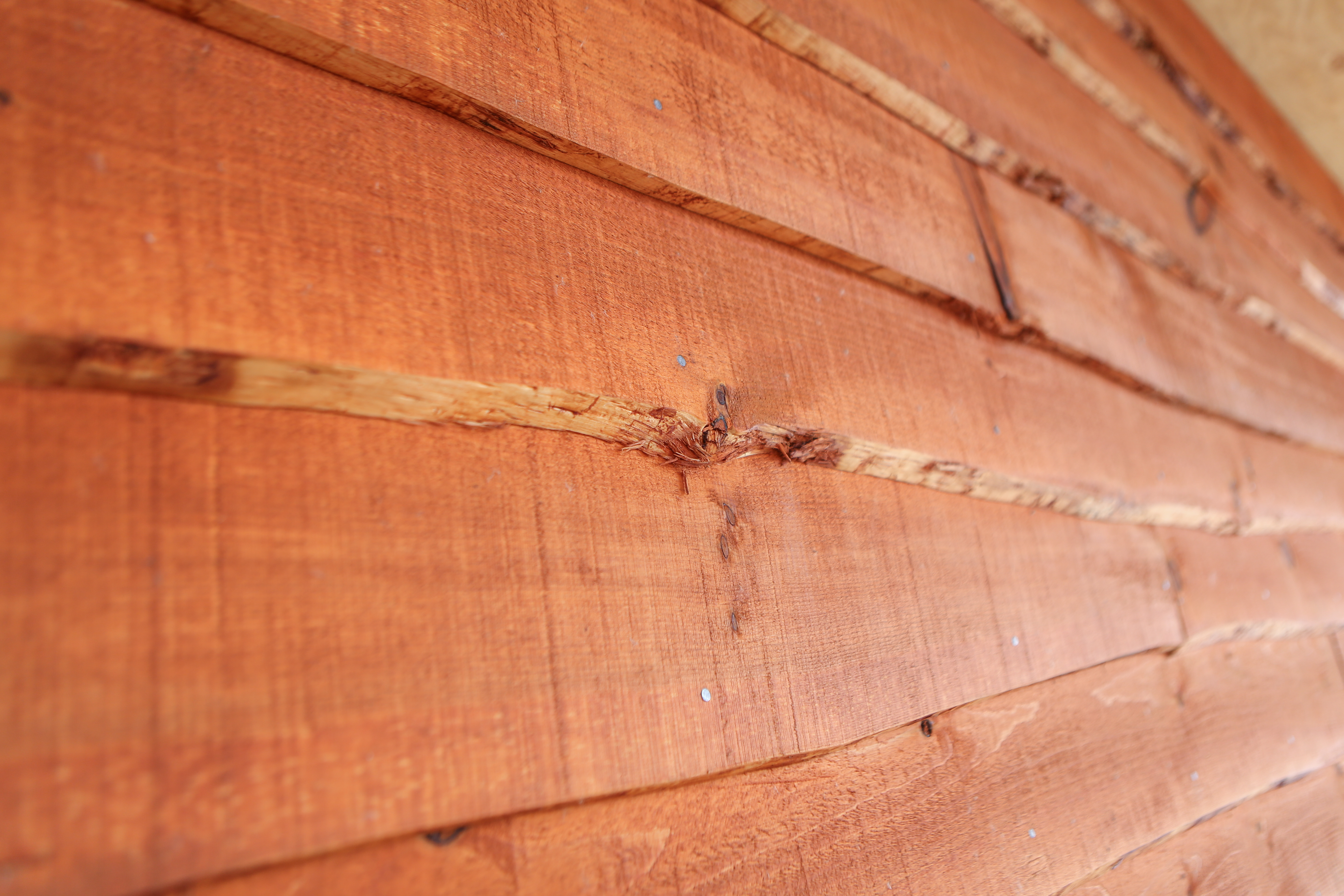Close up of wavy edge siding, pre-stained Ember.