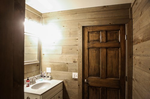 Bathroom with weathered grey shiplap walls.